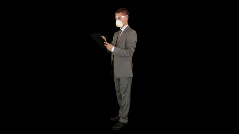 Young businessman with protective glasses and mask taking notes, against black - stock footage