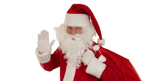 Santa Claus carrying his bag, looks at the camera sends a blow kiss and wave, white