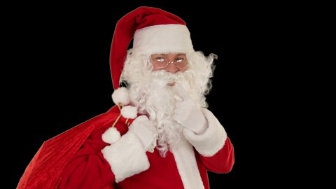 Santa Claus carrying his bag, looks at the camera sends a kiss and wave, black  - stock footage