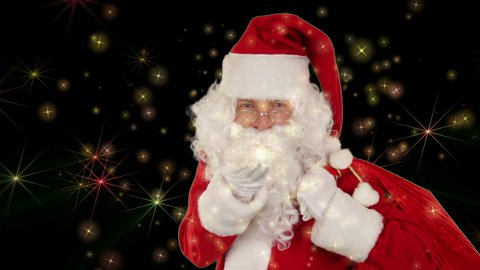 Santa Claus carrying his bag, is looking at the camera and sends a kiss with golden stars  - stock footage