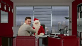 Santa Claus signing a contract with a Businessman, looks at camera and smile