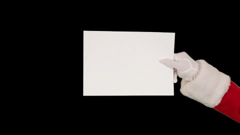 Santa Claus presenting a white sheet, against black