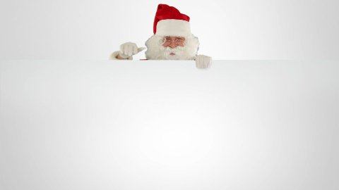 Santa Claus presenting a white sheet with space for text