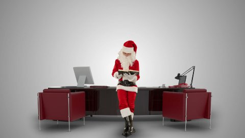 Santa Claus reading a book in his modern Christmas Office, against white - stock footage