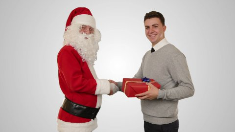 Young Businessman receiving a present from Santa Claus, shaking hands - stock footage