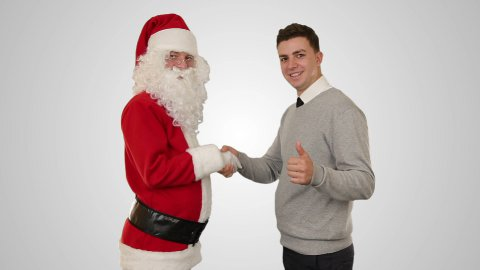 Santa Claus and Young Businessman against white, shaking hands - stock footage