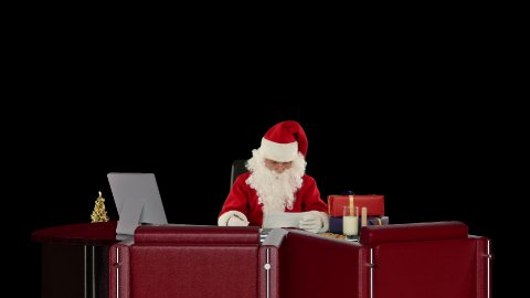 Santa Claus reading letters and sorting presents, against black - stock footage