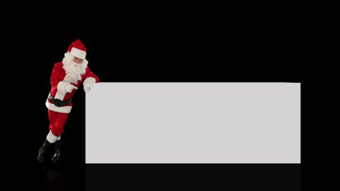 Santa Claus pointing to a white board, against black - stock footage