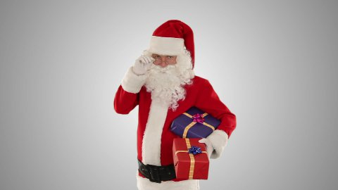 Santa Claus holding presents, against white - stock footage