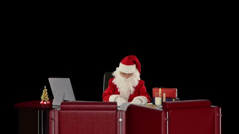 Santa Claus at work, against black - stock footage