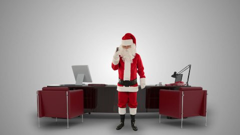 Santa Claus on mobile in his modern Christmas Office, against white - stock footage