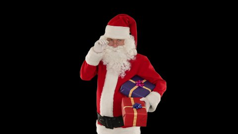 Santa Claus holding presents, against black - stock footage