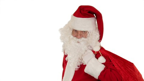 Santa Claus carrying his bag, is looking at the camera, sends a kiss and wave, white - stock footage