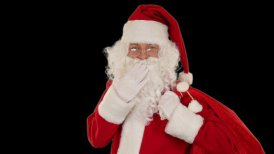 Santa Claus carrying his bag, looks at the camera sends a blow kiss and wave, black