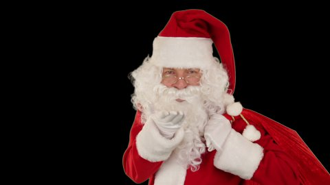 Santa Claus carrying his bag, is looking at the camera, sends a kiss and wave, black - stock footage