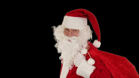 Santa Claus carrying his bag, looks at the camera and winks, black - stock footage