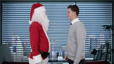 Santa Claus and Young Businessman in a modern office, shaking hands and looking at camera - stock footage