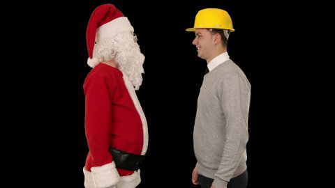 Santa Claus and Young Architect against black, shaking hands and looking at camera - stock footage