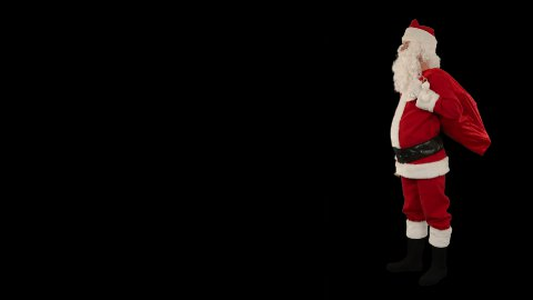 Santa Claus shaking a bell with space for text, against black - stock footage