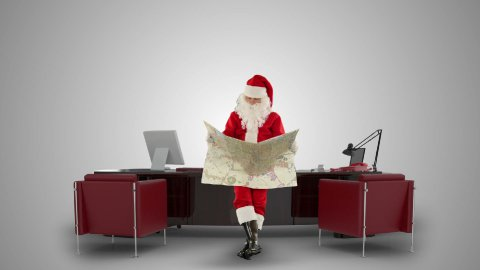 Santa Claus reading a map in his modern Christmas Office, against white - stock footage