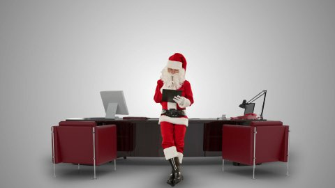 Santa Claus taking notes on a clipboard in his modern Christmas Office, against white - stock footage