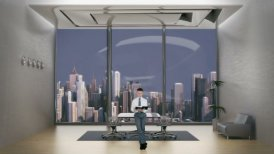 Young Businessman Reading in Office Room with City Skyline in the Background