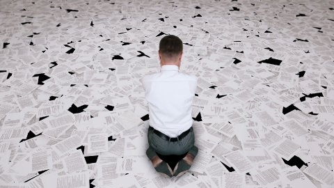 Businessman nightmare, surrounded by bills, back view - stock footage