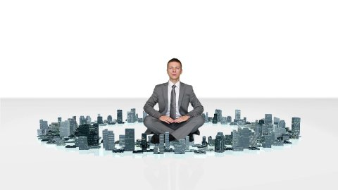 Businessman meditating with buildings rising around him - stock footage