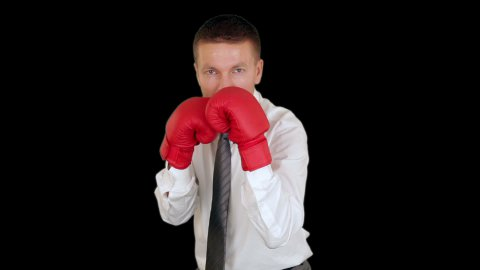 Businessman Boxing against black - stock footage
