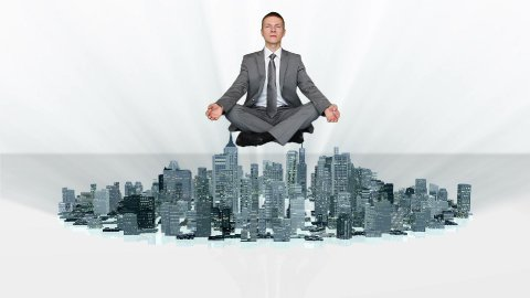 Businessman meditating and slowly rising with city growing around him - stock footage