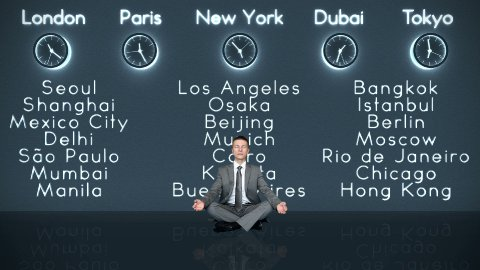 Businessman Meditating with World Clocks and Big Cities on Background in Dark Room - stock footage
