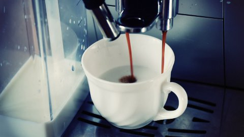 coffee machine pouring cappuccino in cup - stock footage