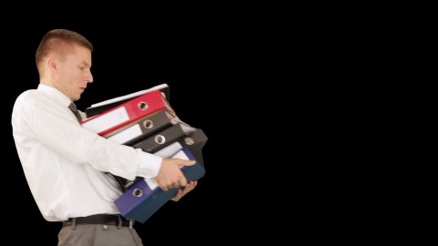 Young businessman carrying files and folders, against black - stock footage