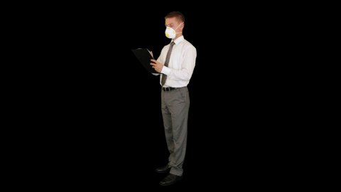 Young businessman, protective glasses and mask taking notes, against black - stock footage