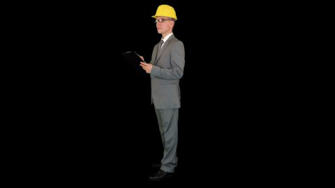 Young architect taking notes on a clipboard, against black - stock footage
