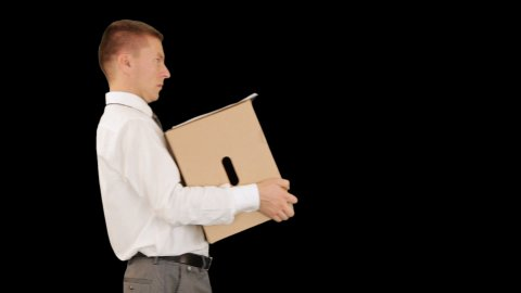 Young businessman carrying a box and falling, against black - stock footage