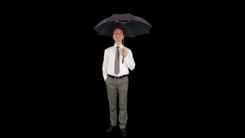 Young businessman opening umbrella, against black - stock footage