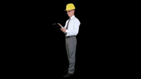 Young architect writing on a clipboard, against black - stock footage
