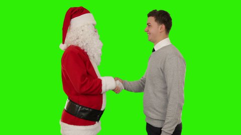 Santa Claus and Young Businessman shaking hands, Green Screen - stock footage