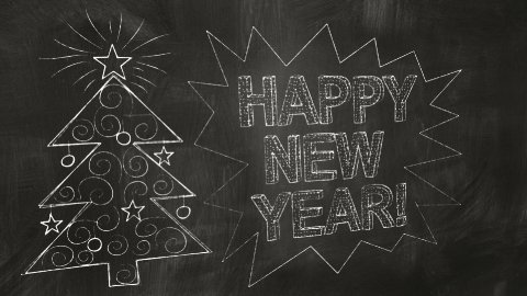 drawing new year greetings on blackboard