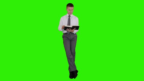 Young businessman reading a book and sitting, Green Screen - stock footage
