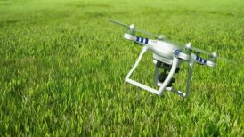 Aerial drone quadcopter flying over green grass.