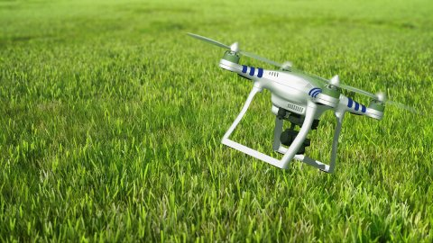 Aerial drone quadcopter flying over green grass. - stock footage