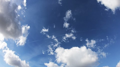 Clouds Moving Across the Blue Sky Against a Background. Timelapse. - stock footage