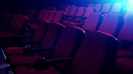 Rows Of Comfortable Red Chairs In Dark Cinema Theater. Loop.